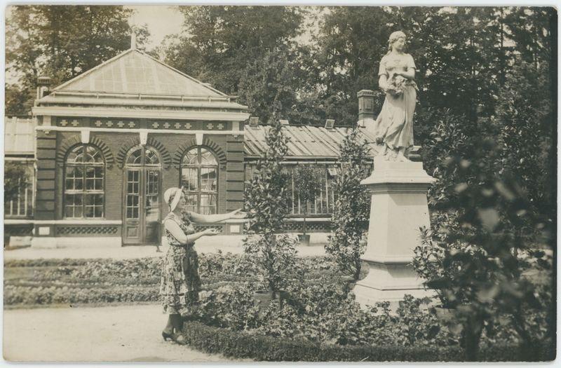 Posąg Flory w parku, w tle budynek oranżerii