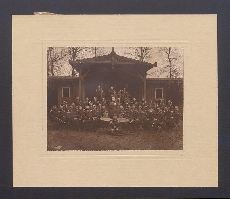 Orkiestra wojskowa 69 Pułku Piechoty na tle altany.
