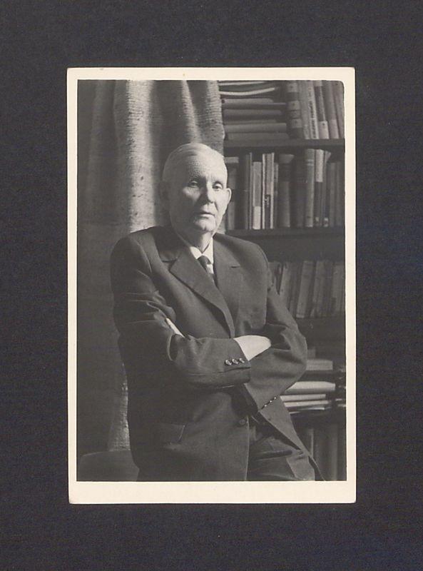 Prof. Bolesław Kasprowicz (junior) na tle regału z książkami.
